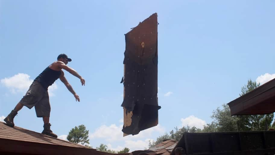 Roofer Throwing Damaged Plywood From A Roof