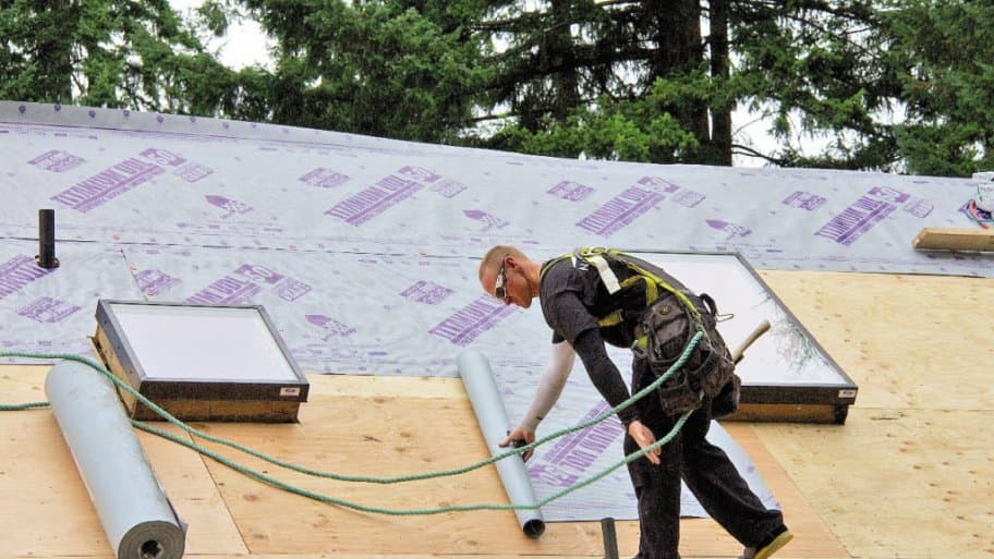 A man lays underlayment on a roof deck.