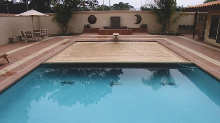 child proof safety cover extending over a swimming pool