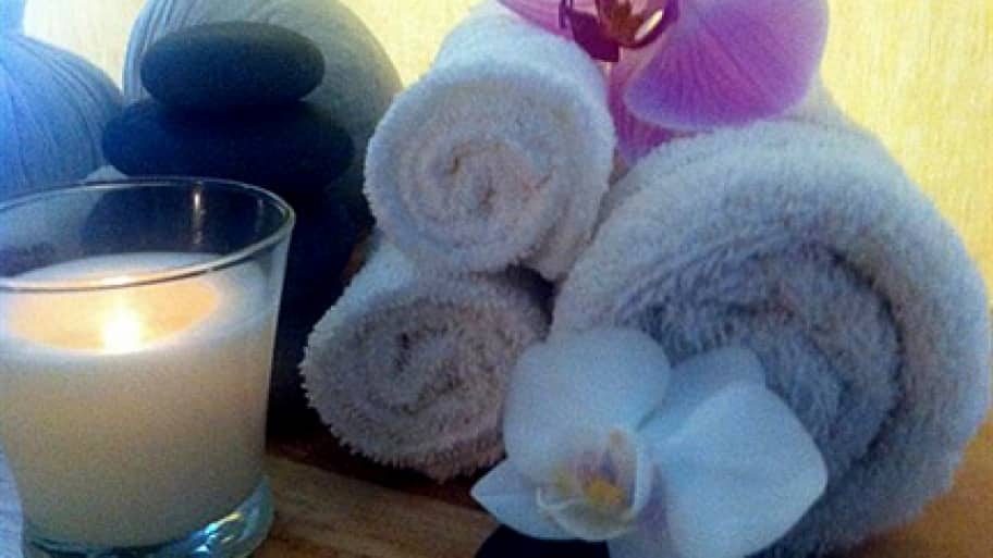 rolled towels, a candle, stones and other supplies for a Shiatsu massage s