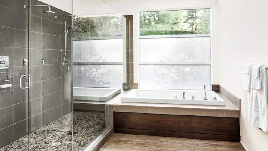 Large glass shower with gray tile, alongside bathtub with wood base