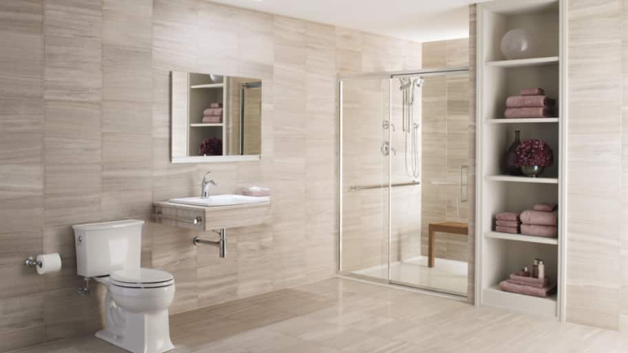 beige bathroom with wall-mounted sink and frameless shower doors