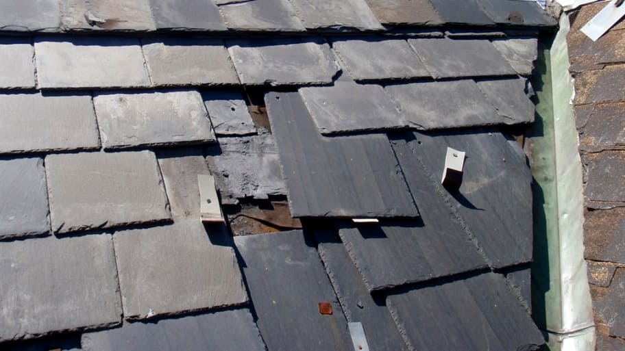 broken slate tiles slipping from roof