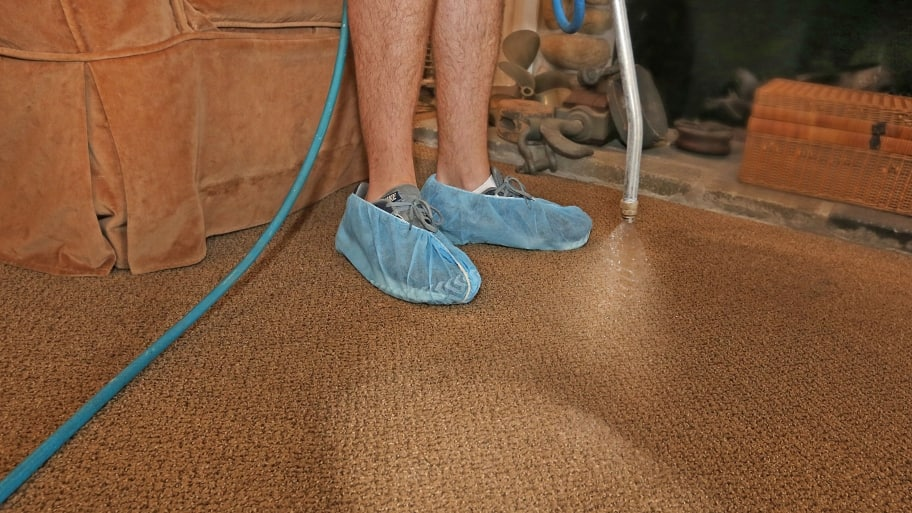 carpet cleaning technician spraying cleaning solution into carpet