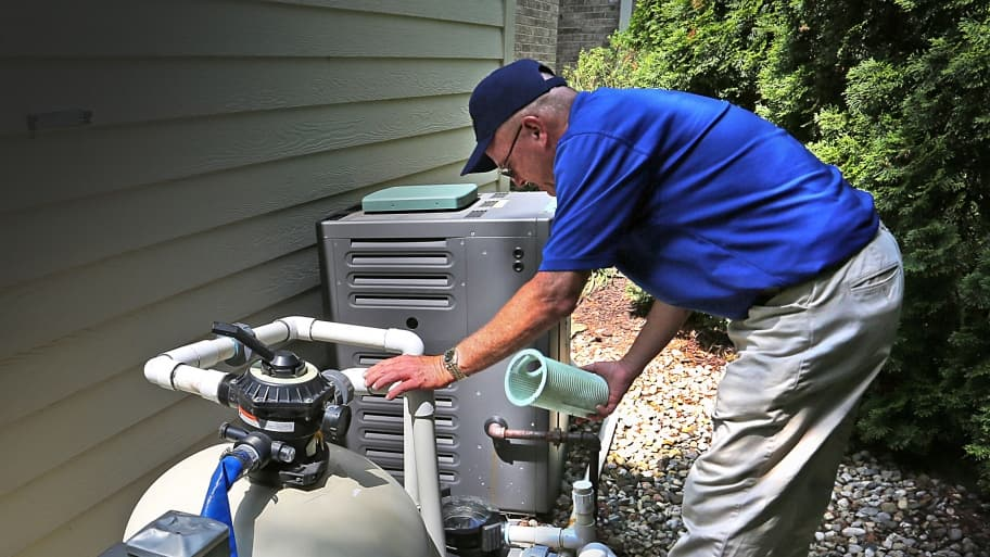 man inspects a residential swimming pool pump and filters during his weekly visit.