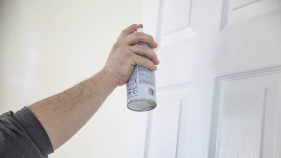 man spray painting door