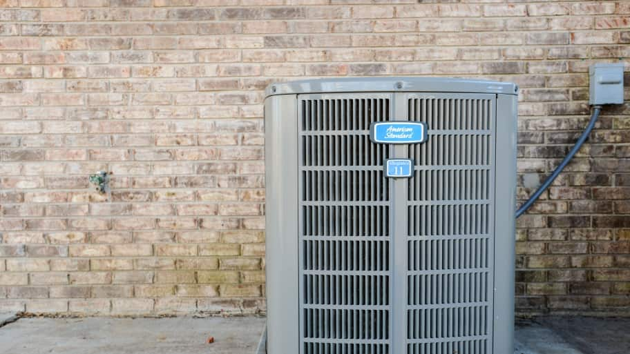 An air conditioning unit sits outside a structure.