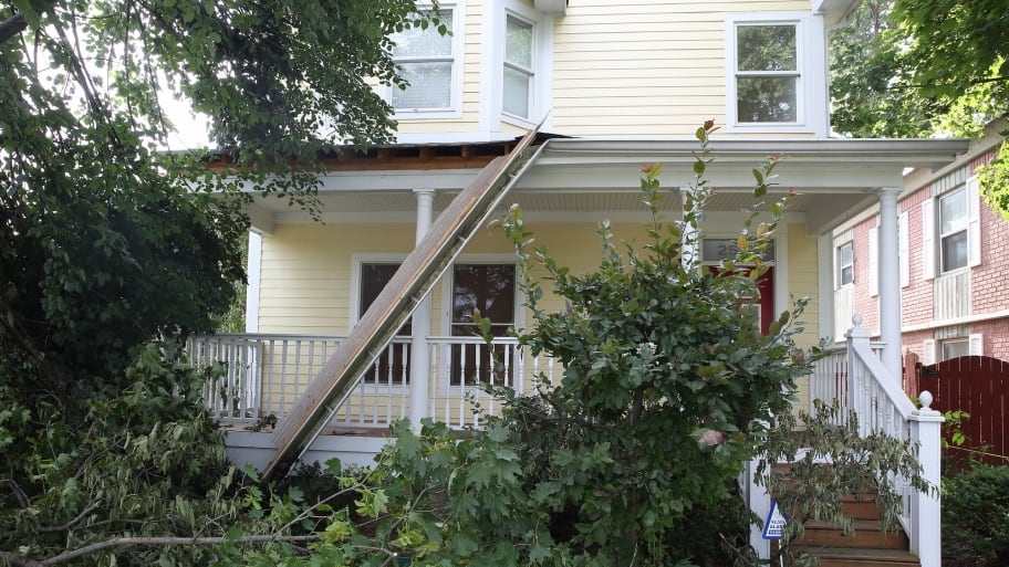 storm damaged home exterior with fallen tree and gutter