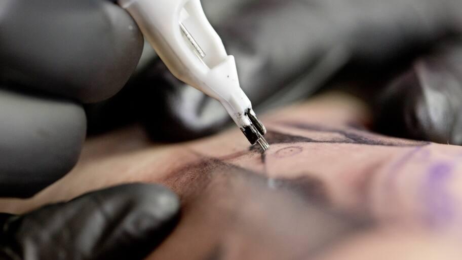 tattoo artist working on a tattoo