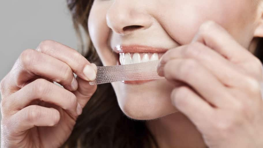 A woman applies a teeth whitening strip to her teeth.
