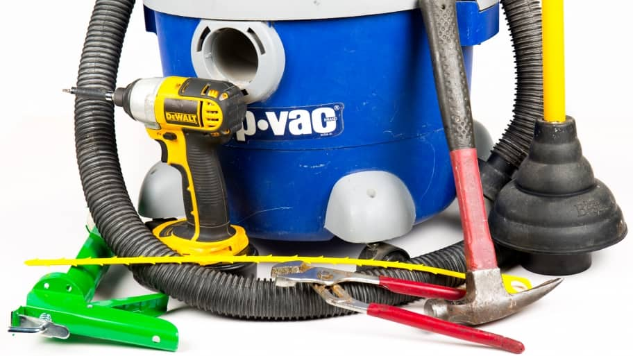 shop vac, cordless drill, hammer, plunger, wrench, zip tie and caulk gun