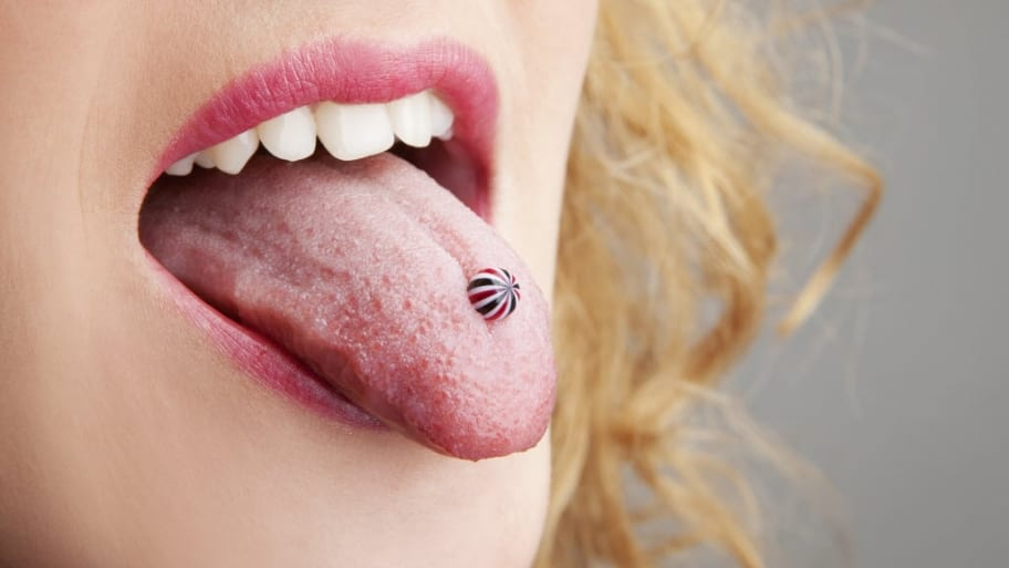Woman sticks out pierced tongue.