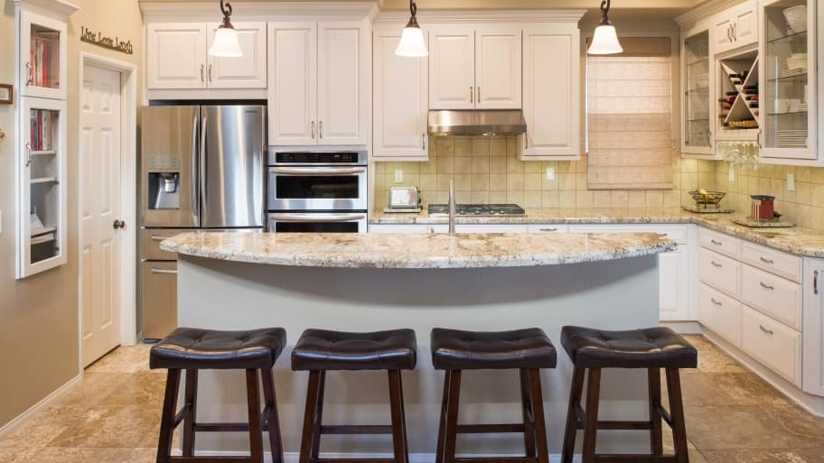 transitional kitchen with quartz countertops, curved kitchen island, steel appliances and contemporary stools