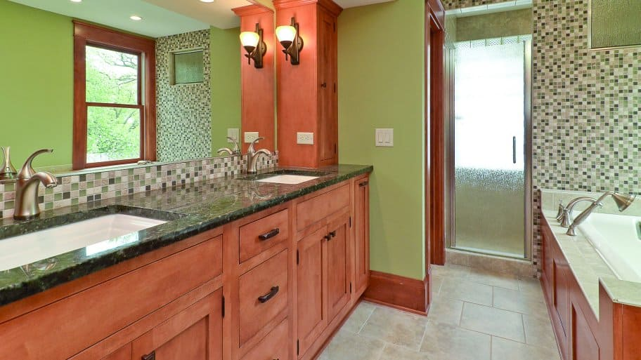 bathroom with brown cabinets and mosaic tile backsplash.