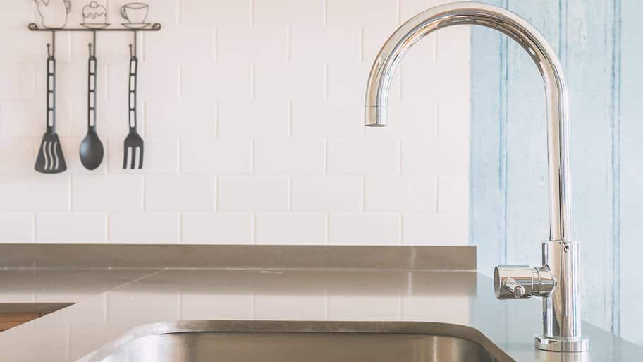 stainless steel faucet and sink with gray countertop