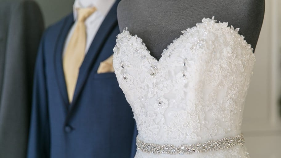 strapless wedding dress with sequins and beads and blue tuxedo in background