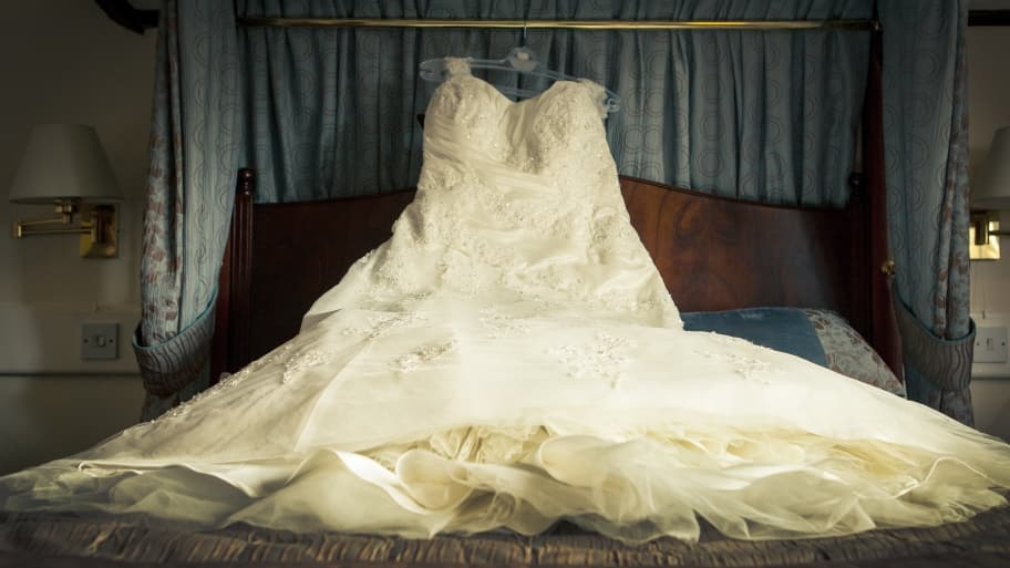 wedding dress on hanger lying across bed