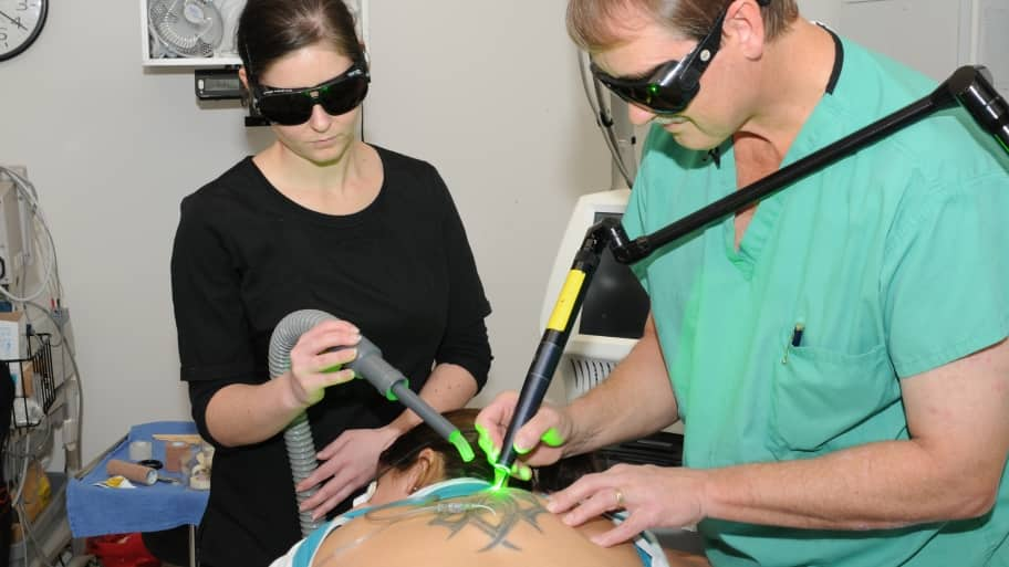 a doctor and assistant remove tattoo with green laser