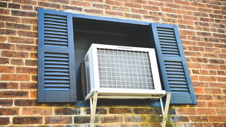 window air conditioner mounted to brick wall