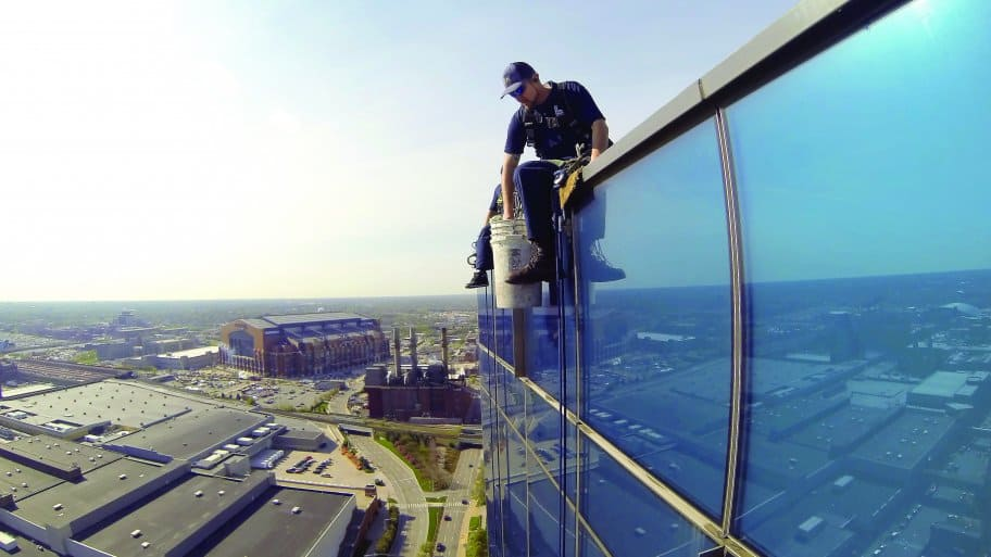 a window washer atop jw marriott in indianapolis with lucas oil stadium in background