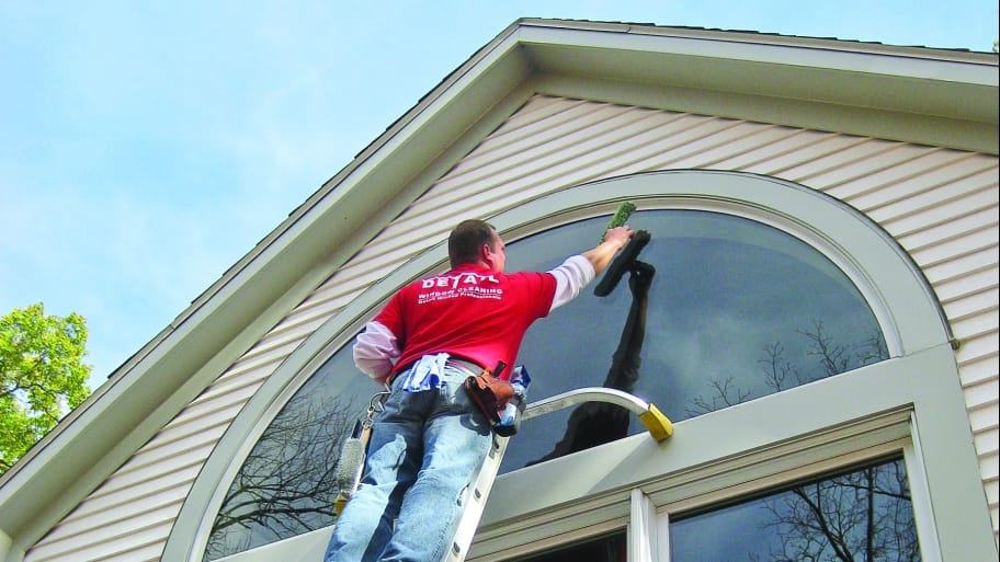 Man On Ladder Washing Exterior Windows On House. Cleaning ...