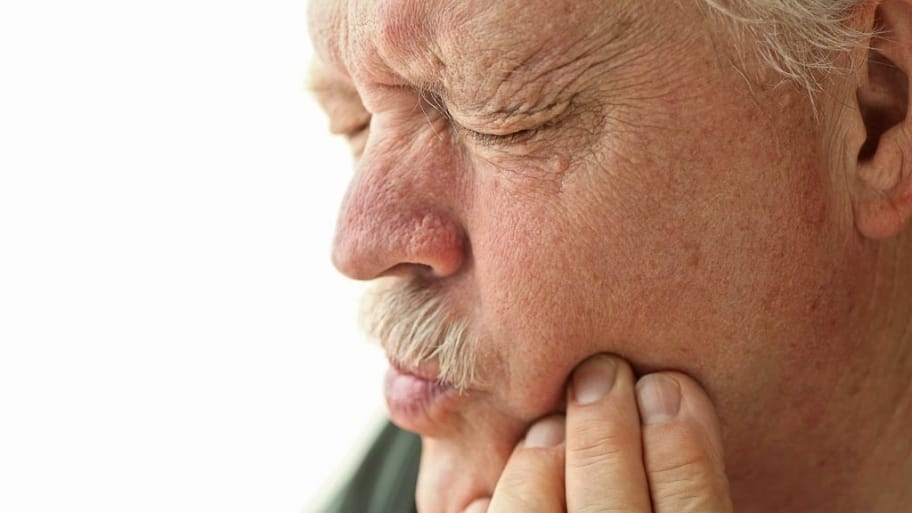 man holding side of his mouth with tooth pain