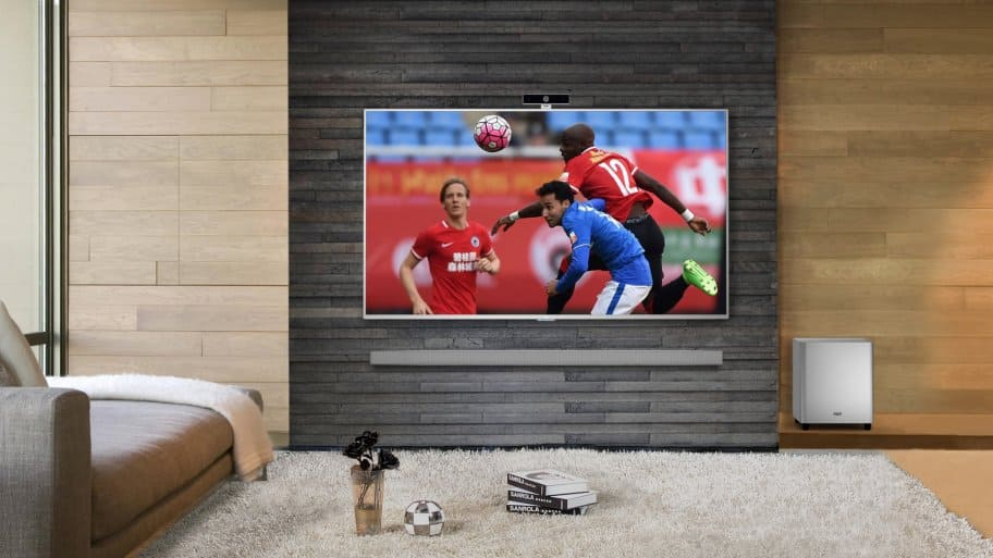 Lifestyle shot of a LeEco 4K Ultra HD TV showing a soccer game, wall mounted in a living room.