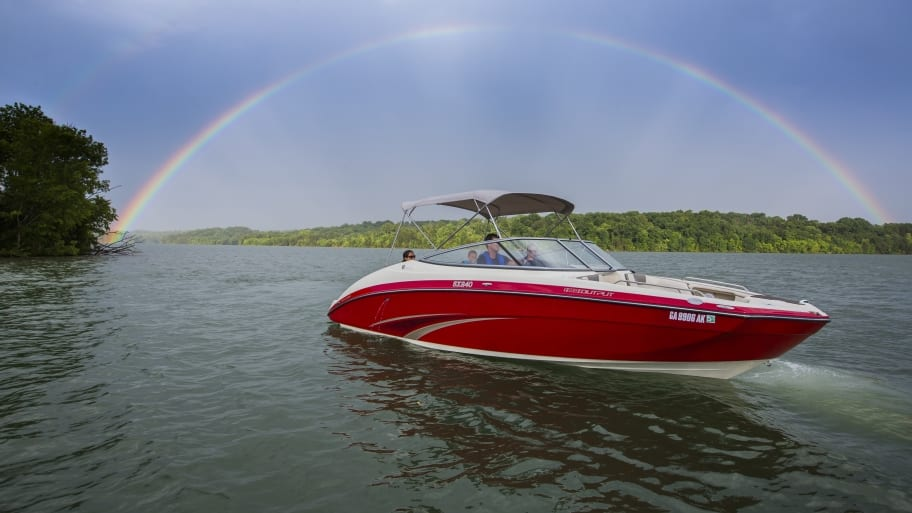 red boat on lake with rainbow