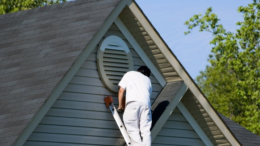 man on ladder painting house