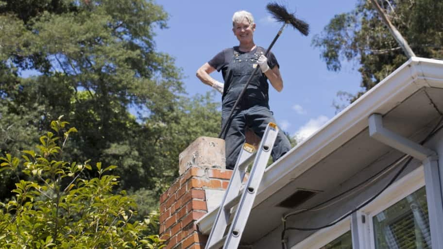 Chimney sweeper atop a roof