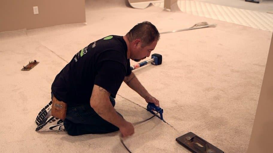 man installs carpet