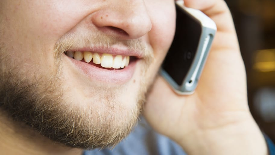 Man with beard talking on cell phone with his smile and teeth