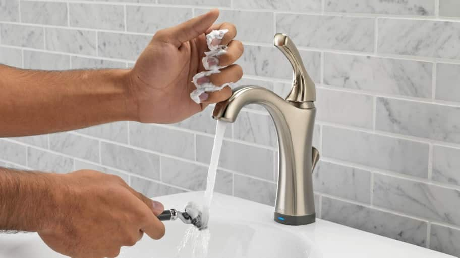 Man rinsing of razor under bathroom faucet.