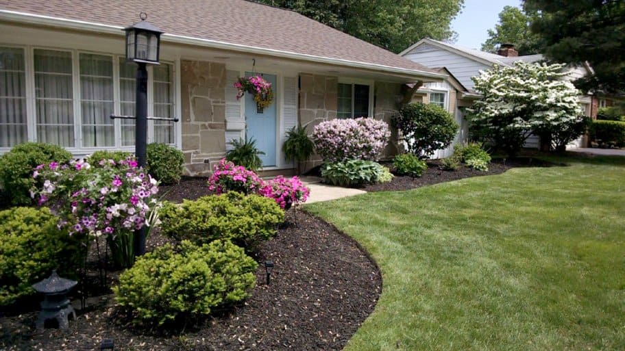 Front Yard Landscape With Edged Flower Beds, Mulch And Post Lamp.