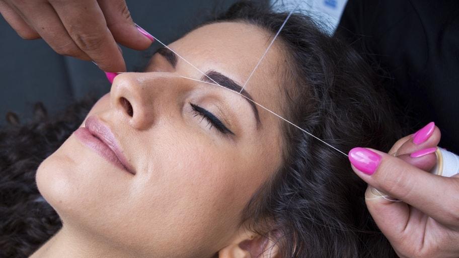 Woman getting eyebrows threaded.