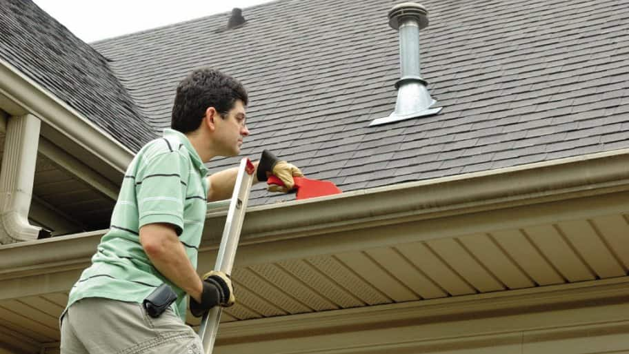 man on ladder cleaning gutter