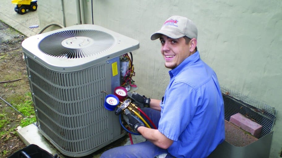 HVAC technician inspects air conditioner.