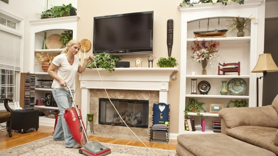 House cleaning employee vacuuming rug