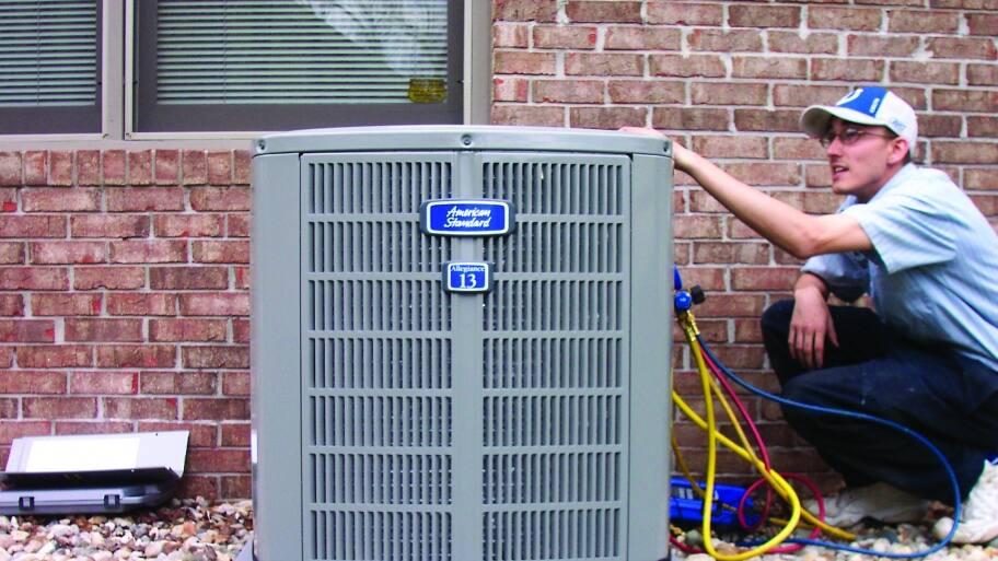HVAC contractor servicing air conditioner