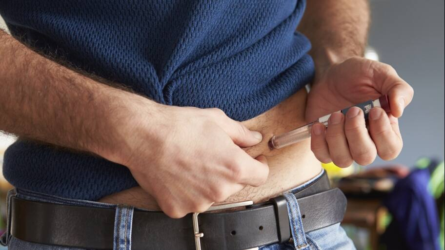 Man giving himself an insulin injection in abdomen