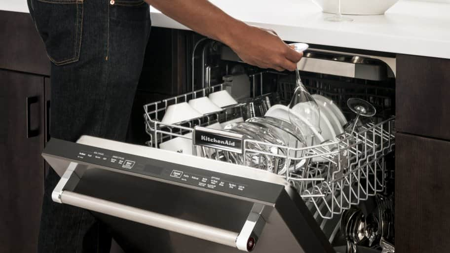 Man Unloading KitchenAid KDTE254EBL Dishwasher.