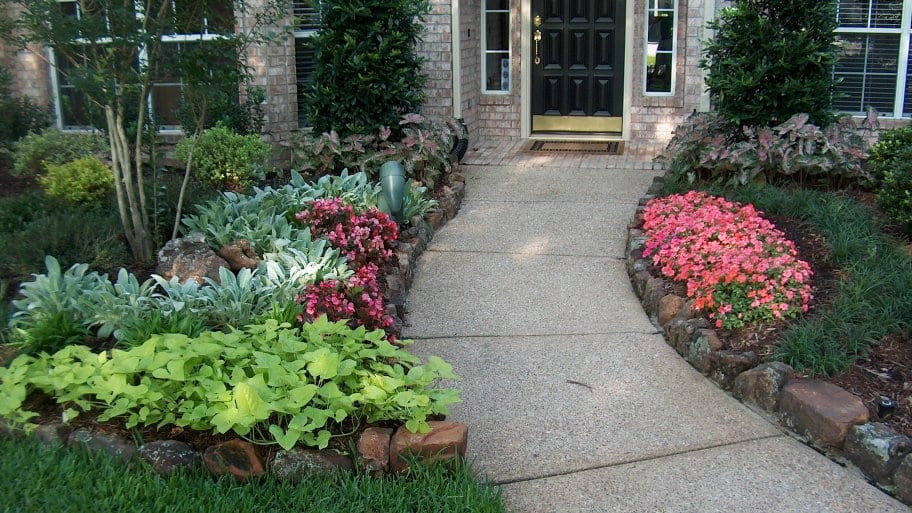 Landscaped Entry With Flowers Trees Shrubs And Brick Edging