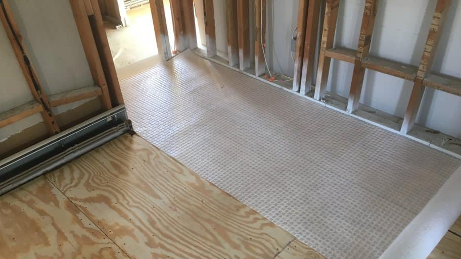 uncoupling membrane rolled out over a plywood floor.
