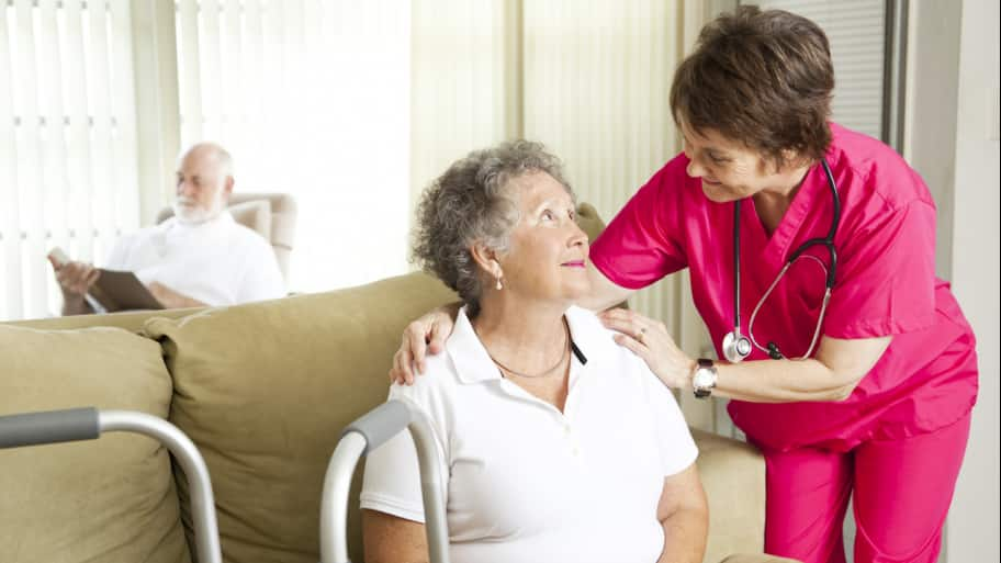 a medical professional talks with a woman in a nursing home facility who is seated on a coach with a walker nearby. (Photo by Photo by Lisa F. Young - Fotolia.com)