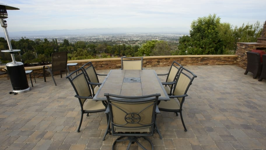 dining table on top of a paver patio with view of the city below.