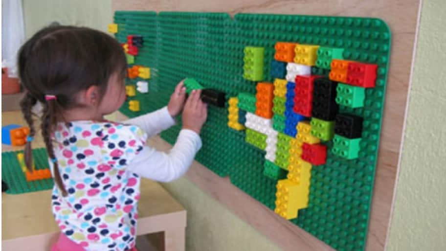little girl playing on Lego wall