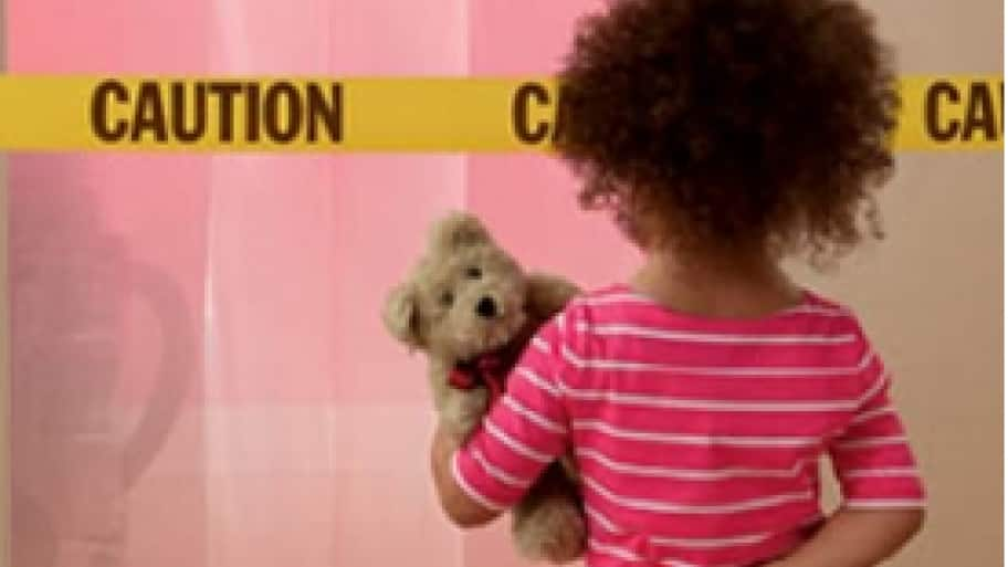girl standing in front of caution tape and screened off room