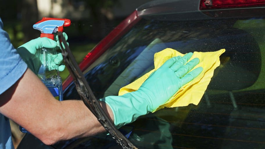 Person cleaning car windows with a microfiber towel