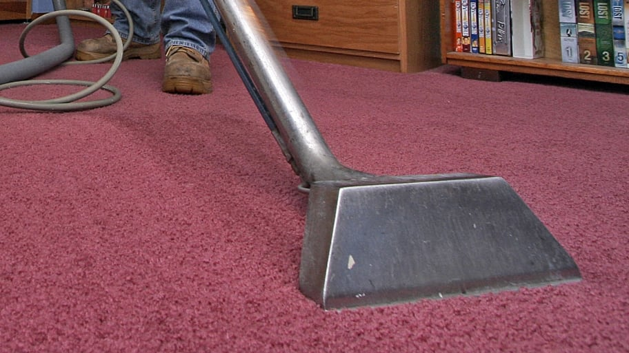 man steam cleaning a carpet