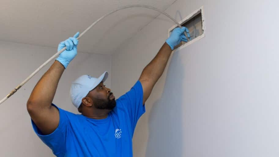 air duct cleaning worker inserting vacuum hose into vent